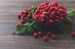 Red fresh raspberries on brown rustic wood background. Raspberries bowl on rustic wood background, copy space. Organic berries with peduncles and green leaves on Stock Photo