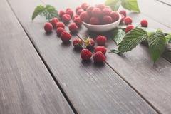 Red fresh raspberries on brown rustic wood background. Raspberries bowl on rustic wood background, copy space. Organic berries on wooden table Stock Images