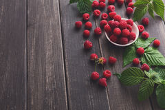 Red fresh raspberries on brown rustic wood background. Raspberries bowl on rustic wood background, copy space. Organic berries on wooden table Royalty Free Stock Images