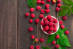 Red fresh raspberries on brown rustic wood background. Bowl with natural ripe organic berries with peduncles and green leaves on wooden table, top view with Royalty Free Stock Image