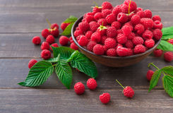 Red fresh raspberries on brown rustic wood background. Bowl with natural ripe organic berries with peduncles and green leaves on wooden table Royalty Free Stock Photo