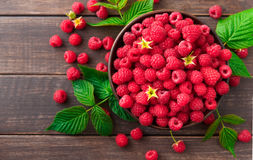 Red fresh raspberries on brown rustic wood background. Bowl with natural ripe organic berries with peduncles and green leaves on wooden table, top view with Stock Image