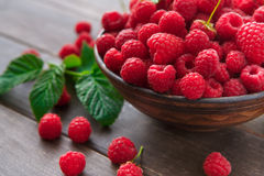 Red fresh raspberries on brown rustic wood background. Bowl with natural ripe organic berries with peduncles and green leaves on wooden table closeup Royalty Free Stock Photography