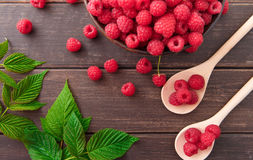 Red fresh raspberries on brown rustic wood background. Bowl with natural ripe organic berries with peduncles, green leaves and wooden spoons on table, top view Stock Photography