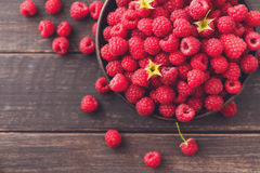 Red fresh raspberries on brown rustic wood background. Raspberries on rustic wood background. Bowl with natural ripe organic berries with peduncles and green Royalty Free Stock Image