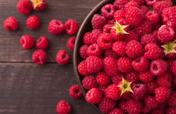 Red fresh raspberries on brown rustic wood background. Fresh raspberries on brown rustic wood background. Bowl with natural ripe organic berries with peduncles Stock Image