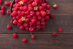 Red fresh raspberries on brown rustic wood background. Raspberries on rustic wood background. Bowl with natural ripe organic berries with peduncles and green Stock Photo