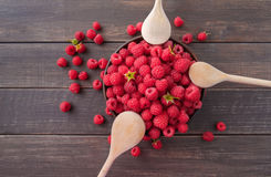 Red fresh raspberries on brown rustic wood background. Bowl with natural ripe organic berries with peduncles and wooden spoons on table, top view, flat lay Stock Photo