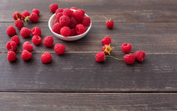 Red fresh raspberries on brown rustic wood background. Bowl with natural ripe organic berries with peduncles on wooden table with copy space Royalty Free Stock Images