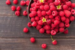 Red fresh raspberries on brown rustic wood background. Bowl with natural ripe organic berries with peduncles on wooden table, top view with copy space Stock Photo