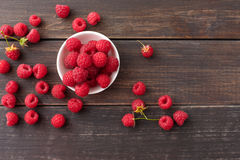 Red fresh raspberries on brown rustic wood background. Bowl with natural ripe organic berries with peduncles on wooden table, top view with copy space Royalty Free Stock Photography