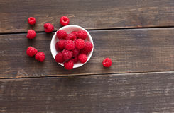 Red fresh raspberries on brown rustic wood background. Bowl with natural ripe organic berries on wooden table, top view with copy space Royalty Free Stock Images