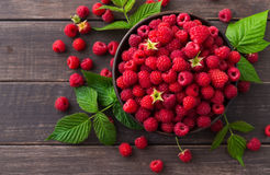 Red fresh raspberries on brown rustic wood background. Raspberries bowl on rustic wood background. Organic berries with peduncles and green leaves on wooden Stock Photography