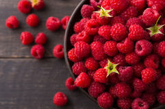 Red fresh raspberries on brown rustic wood background. Raspberries bowl on rustic wood background. Organic berries with peduncles and green leaves on wooden Royalty Free Stock Photography