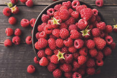 Red fresh raspberries on brown rustic wood background. Raspberries bowl on rustic wood background, top view closeup. Organic berries with peduncles and green Royalty Free Stock Photography