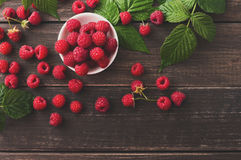 Red fresh raspberries on brown rustic wood background. Raspberries bowl on rustic wood background, top view closeup. Organic berries with peduncles and green Royalty Free Stock Photo