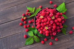 Red fresh raspberries on brown rustic wood background. Raspberries bowl on rustic wood background, top view and copy space. Organic berries with peduncles and Stock Photos
