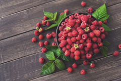 Red fresh raspberries on brown rustic wood background. Raspberries bowl on rustic wood background, top view and copy space. Organic berries with peduncles and Stock Photography