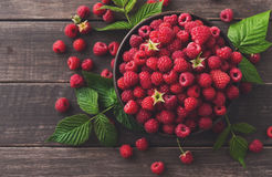 Red fresh raspberries on brown rustic wood background. Raspberries bowl on rustic wood background, top view and copy space. Organic berries with peduncles and Royalty Free Stock Image