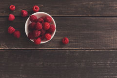 Red fresh raspberries on brown rustic wood background. Raspberries bowl on rustic wood background, top view with copy space. Organic berries on wooden table Royalty Free Stock Images