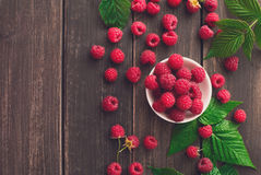 Red fresh raspberries on brown rustic wood background. Raspberries bowl top view on rustic wood background. Organic berries with peduncles and green leaves on Stock Photo
