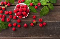 Red fresh raspberries on brown rustic wood background. Raspberries bowl top view on rustic wood background. Organic berries with peduncles and green leaves on Stock Image