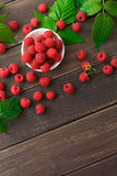 Red fresh raspberries on brown rustic wood background. Raspberries bowl top view on rustic wood background. Organic berries with peduncles and green leaves on Royalty Free Stock Photos