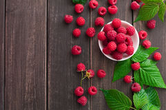 Red fresh raspberries on brown rustic wood background. Raspberries bowl top view on rustic wood background. Organic berries with peduncles and green leaves on Royalty Free Stock Photography