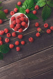 Red fresh raspberries on brown rustic wood background. Raspberries bowl on rustic wood background, top view, vertical image with copy space Royalty Free Stock Images