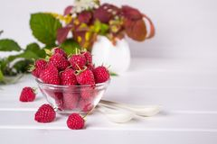 Red fresh raspberries in a glass bowl with green leaves. On white background Stock Photo
