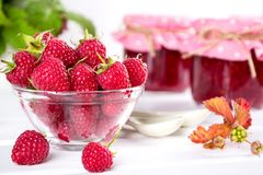 Red fresh raspberries in a glass bowl and Raspberry jam with green leaves Royalty Free Stock Images