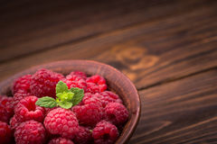 Red fresh raspberries. On rustic wood table Royalty Free Stock Image