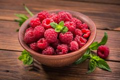 Red fresh raspberries. On rustic wood table Stock Photo