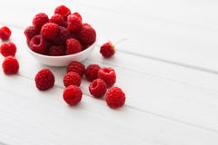 Red fresh raspberries on white rustic wood background. Raspberries bowl on white rustic wood background Royalty Free Stock Images