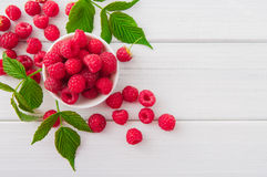 Red fresh raspberries on white rustic wood background. Bowl with natural ripe organic berries with peduncles and green leaves on wooden table, top view with Royalty Free Stock Photos
