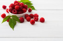 Red fresh raspberries on white rustic wood background. Bowl with natural ripe organic berries with peduncles and green leaves on wooden table, top view with Stock Images