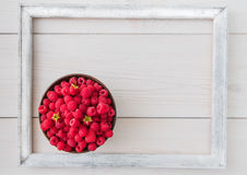 Red fresh raspberries on white rustic wood background. Bowl with natural ripe organic berries with peduncles and white photo frame around it on wooden table Stock Photo