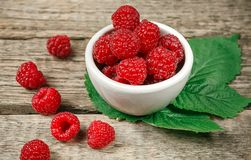 Red fresh raspberries on white rustic wood background. Bowl with. Natural ripe organic berries with peduncles and green leaves on wooden table, top view with Stock Photography