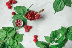 Red fresh raspberries on white rustic wood background. Bowl with. Natural ripe organic berries with peduncles and green leaves on wooden table, top view with Stock Photos