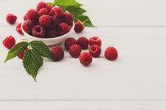 Red fresh raspberries on white rustic wood background. With copy space Stock Photo