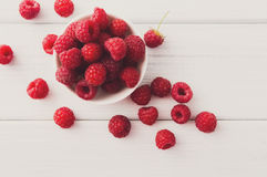 Red fresh raspberries on white rustic wood background. Raspberries top view on white rustic wood background Royalty Free Stock Photo