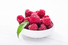 Red fresh raspberry in bowl. On wooden table Stock Photo