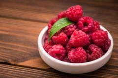Red fresh raspberry in bowl. On wooden table Royalty Free Stock Images