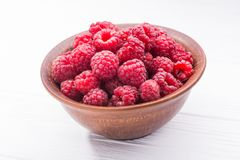 Red fresh raspberry in bowl. On wooden table Royalty Free Stock Photography