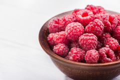 Red fresh raspberry in bowl. On wooden table Royalty Free Stock Image