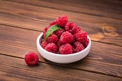 Red fresh raspberry in bowl. On wooden table Stock Image