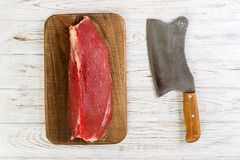 Red fresh raw beef veal fillet on cutting board. white wooden background.  Royalty Free Stock Image