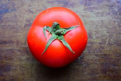 Red juicy tomato on a dark old brown background Stock Photos