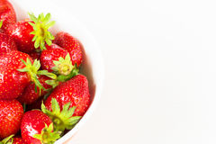 Red fresh strawberries in a bowl isolated on white background. Close up view. Stock Photo