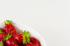 Red fresh strawberries in a bowl isolated on white background. Close up view. Stock Image